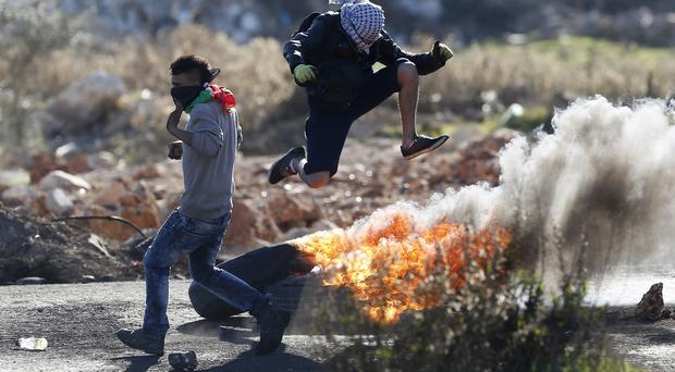 Palestinian protesters during clashes with Israeli troops in the West Bank city of Ramallah (AP)