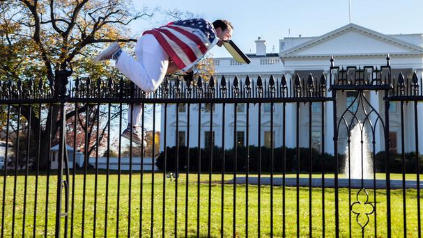 A man with a US flag wrapped around him jumps the fence at the White House (Vanessa Pena/AP)