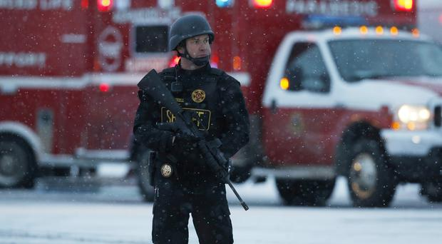 An officer stands guard at a Planned Parenthood in Colorado Springs after a gunman opened fire (AP)
