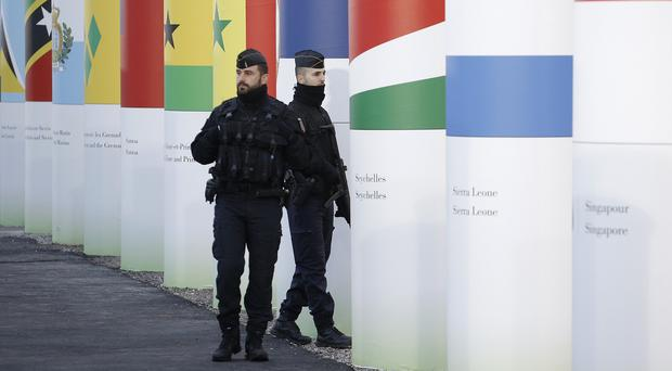 Policemen patrol outside the main entrance of the United Nations Climate Change Conference in Le Bourget, outside Paris (AP)