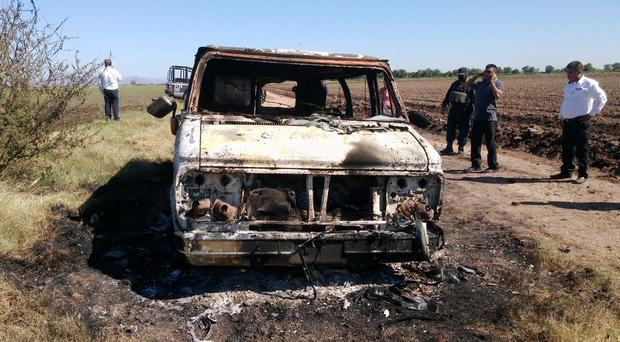 Mexican authorities inspect a burnt out van suspected to belong to two Australian tourists who are missing (AP)