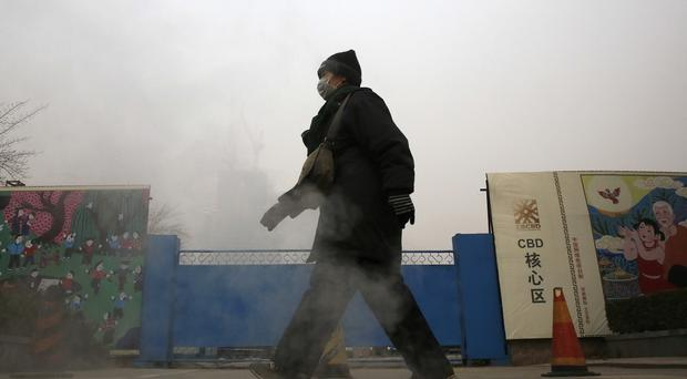 A woman wearing a mask to protect herself from pollutants walks past a construction site on a heavily polluted day in Beijing (AP)