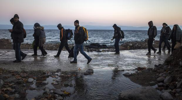 Afghan refugees walk on a beach after their arrival from the Turkish coast to the north-eastern Greek island of Lesbos (AP)