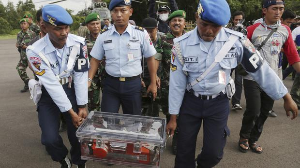 Indonesian air force personnel carry the flight data recorder of AirAsia Flight 8501 that crashed in the Java Sea (AP)