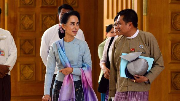 Aung San Suu Kyi talks to a parliament member of her National League for Democracy party (AP)