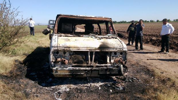 Mexican authorities inspect a burned-out van after the two Australian men went missing (AP)