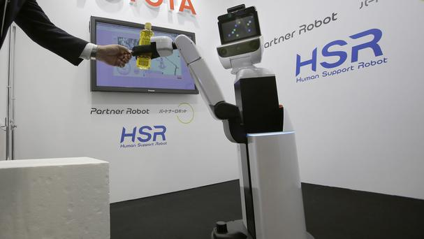 Toyota's HSR, in action at the International Robot exhibition in Tokyo, can pick up after people, bring an item to the bedside or open curtains. (AP)