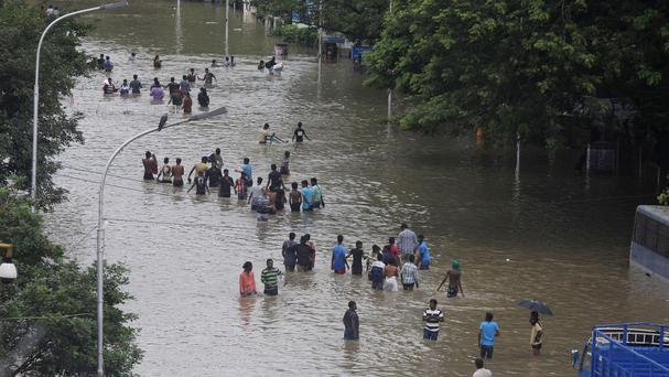 People wade through a flooded road in Chennai, Tamil Nadu, India (AP)