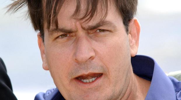 Charlie Sheen is being sued by his ex-fiancee following his announcement that he is HIV positive