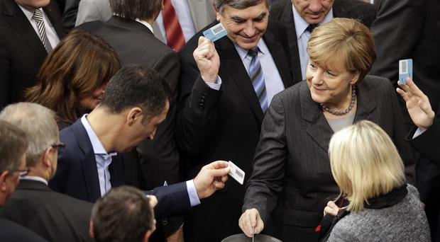 German Chancellor Angela Merkel casts her vote at the German Federal Parliament in Berlin (AP)