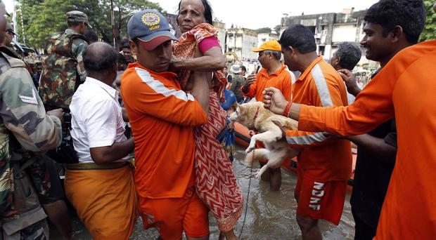 National Disaster Response Force personnel carry an elderly woman and a dog rescued from floodwater in Chennai, in the southern Indian state of Tamil Nadu (AP)