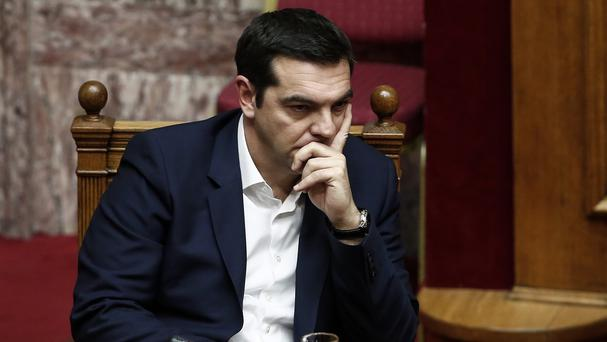 Prime minister Alexis Tsipras in thoughtful mood as parliament passes the government's 2016 budget (AP)