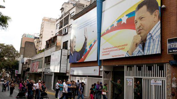 Voters enter a polling station decorated with an image of Venezuela's former president Hugo Chavez, right, and current president Nicolas Maduro. (AP)