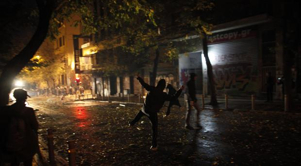 A protester throws an object towards police during riots in the Athens neighbourhood of Exarchia. (AP)