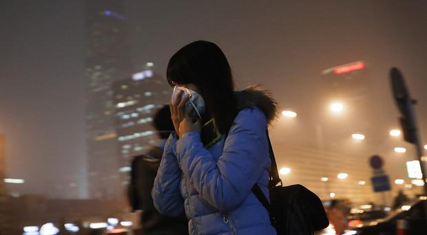 A woman covers her face with a mask as she rushes to a station on a heavily polluted day in Beijing (AP)