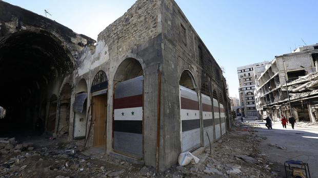 Damaged shops are seen with new doors in the old city of Homs (AP)