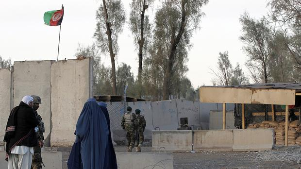 Civilians wait as Afghan security forces guard at the main gate of Kandahar civilian airport. (AP)