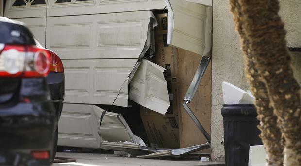 A garage door of Enrique Marquez's home is seen broken in a recent FBI raid. (AP)