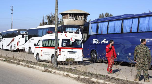 Syrian civilians in a bus convoy leave the Waer neighbourhood of the central city of Homs (AP)