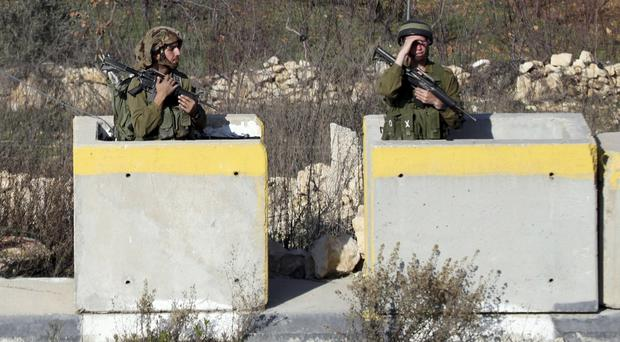 Israeli soldiers stand guard at Halhul checkpoint near Hebron (AP)