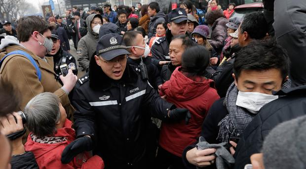Police officers push away supporters of rights lawyer Pu Zhiqiang and foreign journalists near the Beijing Second Intermediate People's Court (AP)