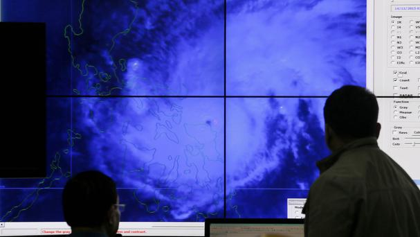 Government meteorologists monitor a satellite image of Typhoon Melor as it hits the eastern Philippines (AP)