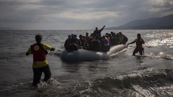 Volunteers rush to assist migrants and refugees as they approach a beach of the Greek island of Lesbos (AP)