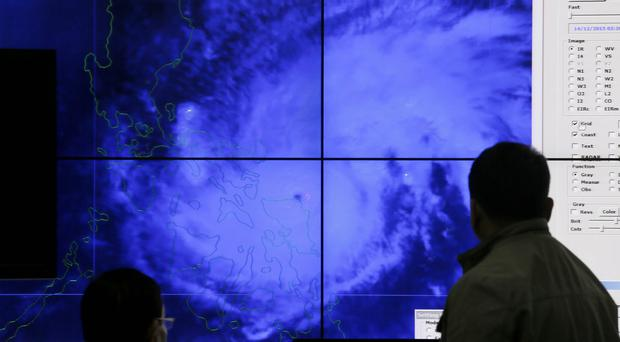 Meteorologists monitor a satellite image of Typhoon Melor at the weather bureau centre in Quezon as it hits the eastern Philippines (AP)