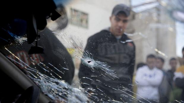 Palestinians a look at a car used in an attempted ramming attack on Israeli soldiers in the Qalandia refugee camp on the outskirts of Ramallah (AP)