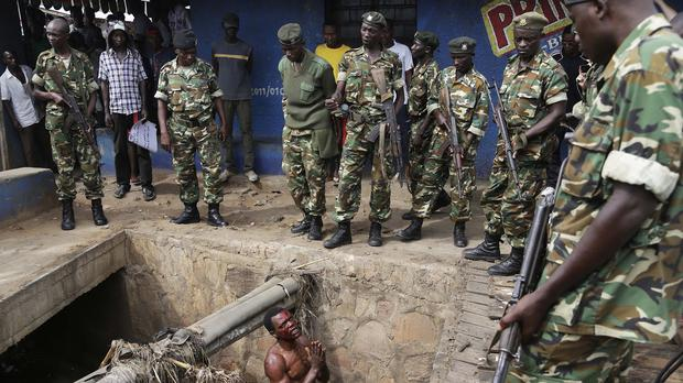 A suspected member of the Burundi ruling party's youth militia pleads with soldiers to protect him from a mob of demonstrators in Bujumbura (AP)
