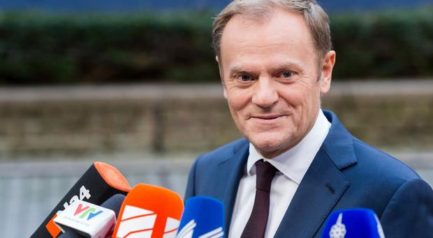 European Council president Donald Tusk speaks with the media as he arrives for an EU summit at the EU Council building in Brussels (AP)