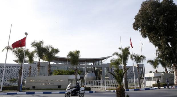 A police officer rides his motorcycle in front of the International Conference Centre in Morocco where the signing of the deal took place (AP)