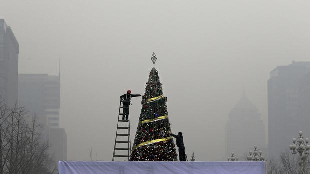 Workers put up a Christmas tree outside a shopping mall during a heavily-polluted day in Beijing (AP)