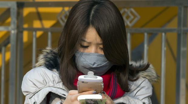A woman wears a mask during a polluted day in Beijing as the Chinese capital issued its second smog red alert of the month (AP)
