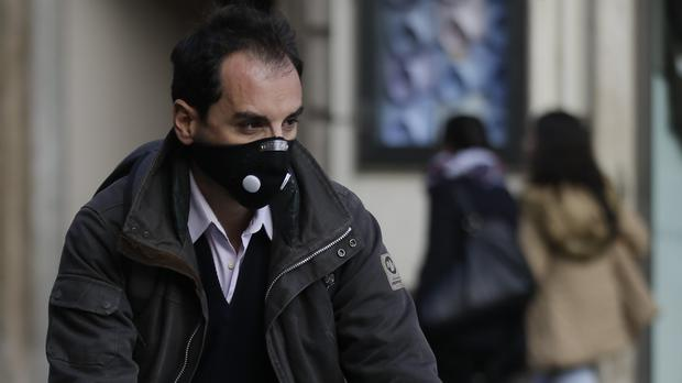 A cyclist wears a protective mask as he pedals in Rome (AP)