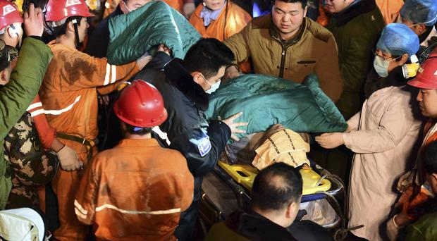A trapped miner is rescued from a collapsed gypsum mine in Pingyi County, China's (Guo Xulei/Xinhua via AP)