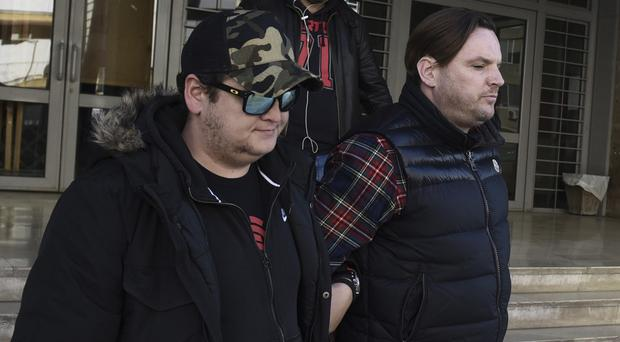 Simon Dutton (right) is escorted by police officers as he leaves a courthouse at the northern Greek city of Thessaloniki (AP)