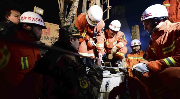 Rescuers try to contact the trapped people at the collapsed mine (Xinhua News Agency/AP)
