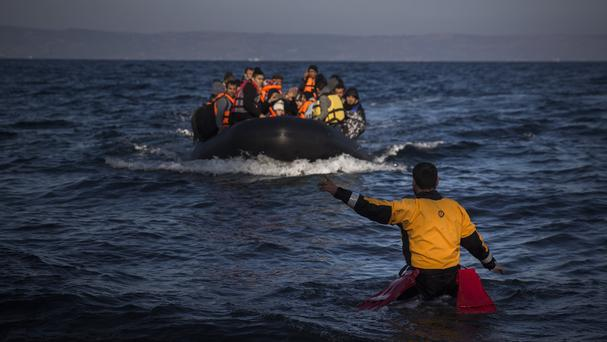 A volunteer lifeguard shows the way to a boat overcrowded with refugees as they approach the Greek island of Lesbos (AP)
