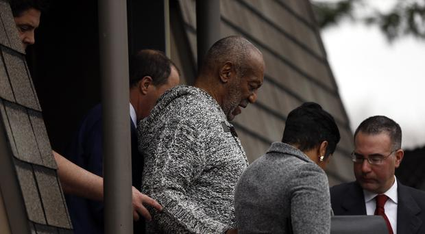 Bill Cosby, centre, leaves the Cheltenham Township Police Department where he was processed after being arraigned on assault charges in Elkins Park, Philadelphia (AP)