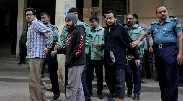 Bangladeshi policemen escort three of the eight people accused of killing an atheist blogger in 2013, to a court in Dhaka, Bangladesh (AP)