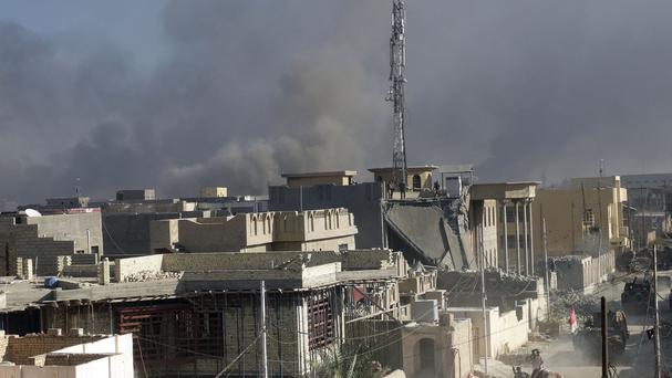 Smoke rises as Iraqi security forces attack the government complex in central Ramadi (AP)