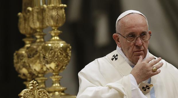 Pope Francis makes the sign of the cross as he celebrates a New Year mass in St Peter's Basilica at the Vatican (AP)