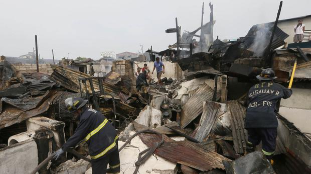 Firemen search through debris amidst still-smouldering houses following an early morning fire that engulfed the neighbourhood of Tondo (AP)
