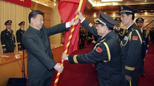 President Xi Jinping, left, presents a military flag to Wei Fenghe, commander of the Rocket Force of the Chinese People's Liberation Army, and Wang Jiasheng, political commissar of the Rocket Force, in Beijing (Xinhua/AP)
