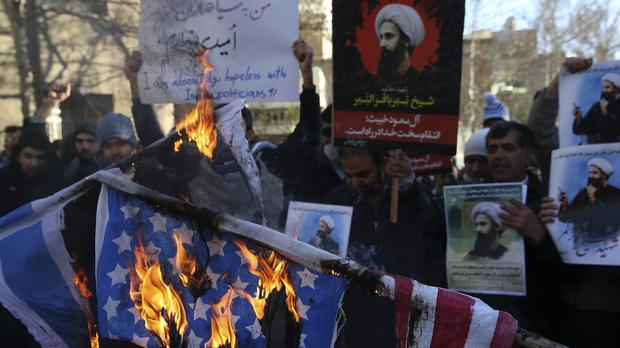 Iranian demonstrators burn representations of the US and Israeli flags in front of the Saudi embassy in Tehran (AP)