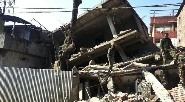 Soldiers inspect a house that collapsed in the earthquake in Imphal, capital of Manipur state (AP)