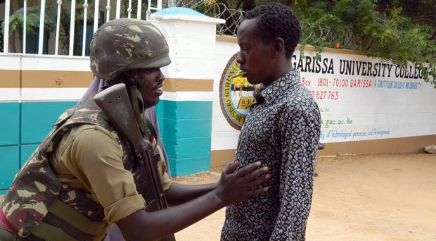 An armed security officer checks a student entering Garissa University College in Kenya. (AP)