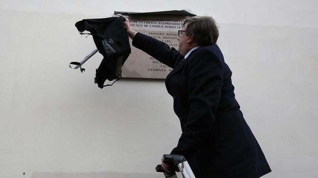 A man removes the covering on a plaque earlier unveiled by French president Francois Hollande outside satirical newspaper Charlie Hebdo's former office (AP)