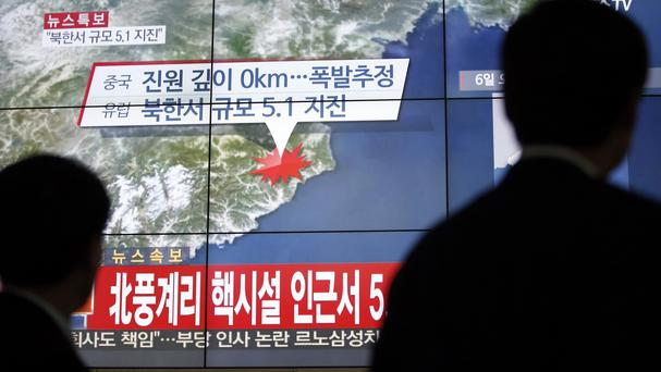 People in Seoul walk by a screen showing the news reporting on an earthquake near North Korea's nuclear facility (AP)